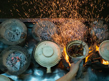 Street Hawker Cooking with Sparks Flying. A street hawker cooking claypot chicken rice sends sparks flying as new charcoal burns down Royalty Free Stock Image