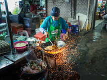 Street Hawker Cooks Char Kway Teow with Sparks Flying from Wok. A Street Hawker cooks Char Kway Teow with sparks flying from underneath his wok. Sparks come from Royalty Free Stock Photography