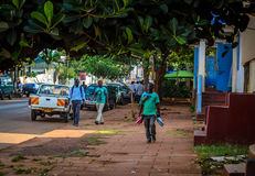 Street hawker. Jinja, Uganda -September 2015 - A young street shoe hawker walks passed a building. Unemployment among the youth of the country, who make up 79% royalty free stock photography