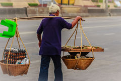 Street hawker is walking with carry bamboo baskets of grilled eg Royalty Free Stock Images