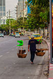 Street hawker is walking with carry bamboo baskets of grilled eg Royalty Free Stock Image