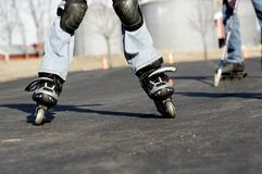 Street hockey. Low angle and view of kids playing street hockey with skates and hockey sticks stock photos