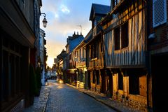 Street in Honfleur, Normandy, France at sunrise. Picturesque street in the Normandy town of Honfleur, France with light of the rising sun Stock Images