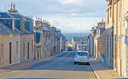 Street in Hopeman. View down Harbour  street in Hopeman with a passing ship in the Moray Firth. A village on the Scottish East Coast tourist route Stock Image
