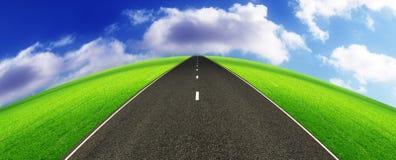 Street horizon. A highway crossing a lush green landscape towards the horizon Stock Photo