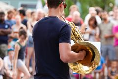 Street horn player. A back portrait of a street horn player with the audience in the background royalty free stock photos