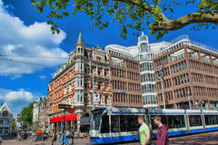 Street with the house in Amsterdam with tram on a day. Royalty Free Stock Photos