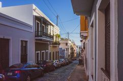 Street and houses in old San Juan. San Juan, Puerto Rico, USA - Jan. 2, 2018: View of street with parked cars between traditional houses in Old San Juan stock photos