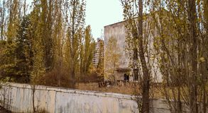 Street and houses among the trees in the empty deserted abandoned town of Pripyat in Ukraine stock photo