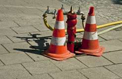 Street hydrant with traffic cones. A red street hydrant ready to work, equipped with faucets, valves and pipes between two traffic cones stock photos