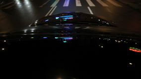 Street illumination on car hood. Light reflections on car glass and hood