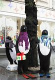 Street installation large toy penguins near tree royalty free stock photography