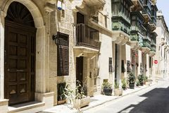 Street on the island of Malta. Typical narrow street on the island of Malta. Buildings with traditional colorful maltese balconies in historical part of Valletta Stock Images