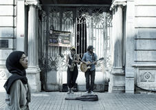 Street jazz musicians woman and man. Play a saxophone and guitar in front of a historical old building on Istiklal avenue in Beyoglu Istanbul. Arabic woman Royalty Free Stock Photography