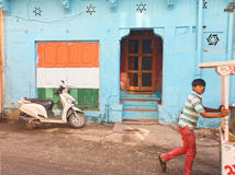 Street in Jodhpur, India. Indian flag and boy on Jodhpur street. Rajasthan, India Royalty Free Stock Photo