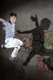 Street jumping. Jumping boy with shadow in front of a wall stock photo