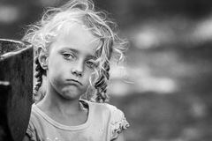 Street kid - candid portrait of a little girl in black and white. Candid portrait of a little girl standing apart and jealously watching other children playing stock photography