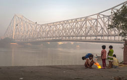 Street kids keep warm on a cold foggy winter morning at Mallick ghat near Howrah bridge at the bank of river Hooghly. Stock Image