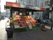 Street kiosk selling fruits Oxford street London. A man arranging his kiosk in Oxford Street London to sell fruit in the morning Royalty Free Stock Image