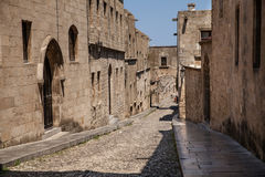Street of knights in Rhodes city. Ruins of the castle and city walls of Rhodes. Narrow streets of the old town. Stock Photos