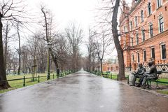 A street of Krakow in a winter day, on the right a characteristic bronze sculpture, Poland Stock Images