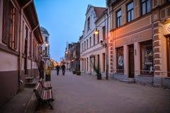 Street in Kuldiga, Latvia. Street of Kuldiga, Latvia at dusk. Dark blue skies, nice buildings, lanterns, a couple walking Stock Image
