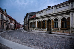 Street in Kuldiga, Latvia. Lonely street of Kuldiga old town, Latvia. Beautiful old buildings and pebble stone pathway with motorcycle seen far away Stock Photos
