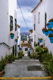 Street with ladders decorated with flowers and spots at white traditional spanish village Mijas Royalty Free Stock Photography