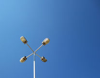 Street lamp. With four hands against pure blue sky Stock Images