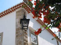 Street Lamp. Ancient Óbidos village,inside the thick walls of an ancient castle, in Portugal. International visitors and tourists from all over the world come Stock Image