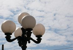 Street lamp against a cloudy sky. Street lamp post against a sky partly filled with clouds on a sunny day Stock Photos