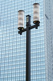 Street lamp against the facade of a modern skyscraper Stock Images