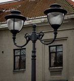 Street lamp against the house. Street lamp against the gray house with a tiled roof Royalty Free Stock Images