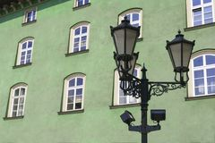 Street lamp in front of green-wall windows Stock Photo