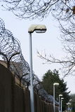 Street lamp beside barbed wire fence stretched around prison walls Royalty Free Stock Photos