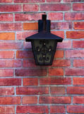 Street lamp on a brick wall. A metal street-lamp on a red brick wall Royalty Free Stock Image