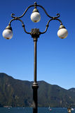 Street lamp a bulb in the   sky lake of lugano Royalty Free Stock Images