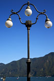 Street lamp a bulb in the   sky lake of lugano Switzerland Royalty Free Stock Images