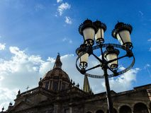 Street lamp, cathedral, sky and clouds at sunset stock images