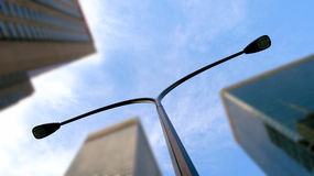 Street lamp in city. A view looking upward at a modern street light with high-rise buildings of the city of Montreal in the background royalty free stock photos