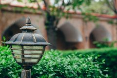 Street lamp close up on a background of plants royalty free stock photo