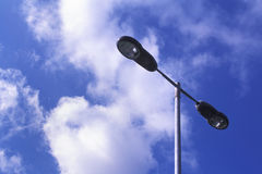 Street Lamp at Day Time. A street lamp at day time, under a blue sky with white clouds Stock Photo