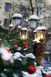 Street lamp decorated with christmas staff pine cones, red berries, fir bunch. New year background royalty free stock photography