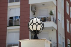 Street lamp in the form of a ball in the forged frame in the summer sun Stock Photo