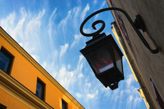 Street lamp on the front of the building on a background of clou Royalty Free Stock Photography