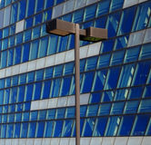 Street lamp in front of a glass building Stock Photos