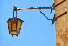 A street lamp on the house wall in Mdina. Malta. An old style metal street lamp hanging on the wall of a residential house in Mdina. Malta Royalty Free Stock Photo