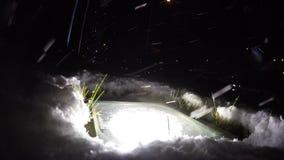 Street lamp illuminates the snow. Green grass under the snow stock video footage