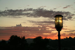 A street lamp illuminating at sunset. An older street lamp illuminating at sunset with fiery orange clouds in the background Stock Image