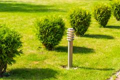 Street lamp on a lawn., horizontal frame. Street metal chrome lamp on the lawn, horizontal frame royalty free stock photography